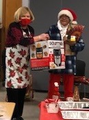 A class participant receives an air fryer from Linda, left, during the nutrition class holiday gathering.