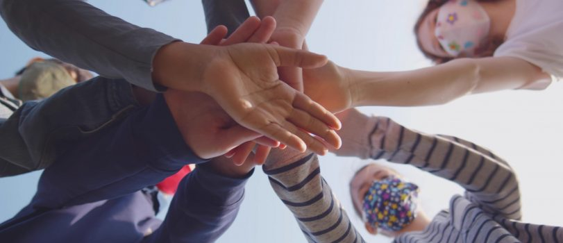 Bottom view of diverse schoolchildren in mask putting hands together outdoors. Preteen classmates in safety mask putting hands together over blue sky background